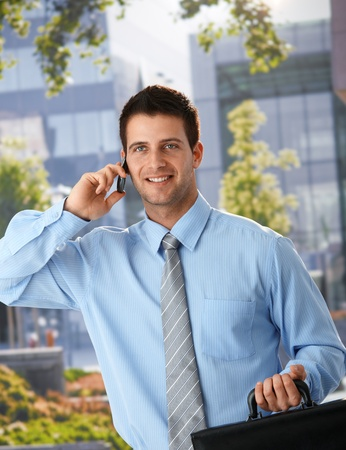 Happy businessman standing outside of office, speaking on mobile phone, holding briefcase. photo