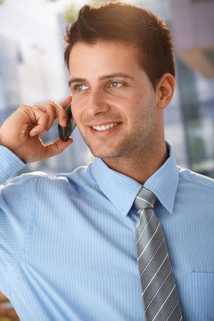 Sunny outdoor portrait of handsome businessman talking on mobile phone, smiling. photo