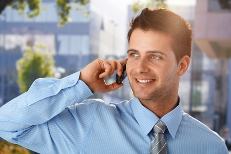 Outdoor spring portrait of smiling businessman speaking on cellphone in front of office building. photo