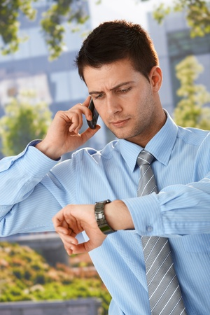 Businessman on phone call checking time on watch, looking worried, standing outside of office. Stock Photo - 9564406