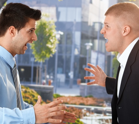 front facing: Angry businessmen standing facing each other, shouting and gesturing in front of office. Stock Photo
