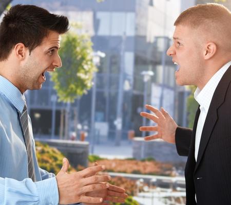 ciascuno: Angry imprenditori in piedi uno di fronte all'altro, urlando e gesticolando davanti all'ufficio. Archivio Fotografico