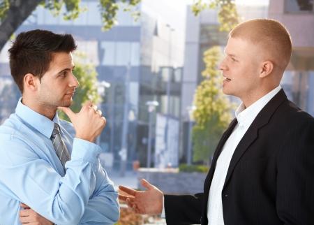 prestar atencion: Empresarios charlando fuera del edificio de oficinas disfrutando de vacaciones.