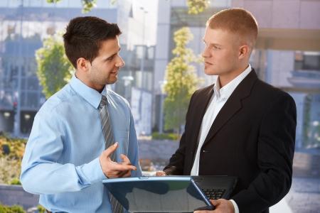 dos personas hablando: Empresario explicando el trabajo de equipo de colega en portátil, permanente fuera del edificio de oficinas.