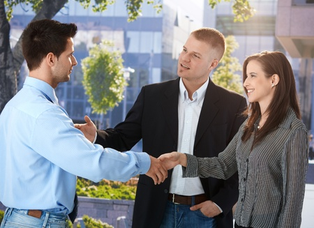 coworker: Businesspeople meeting outside of office, businessman introducing female colleague, smiling.