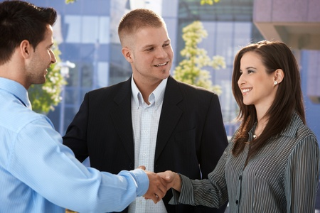 introducing: Businesspeople introducing outside of office, shaking hand, smiling. Stock Photo