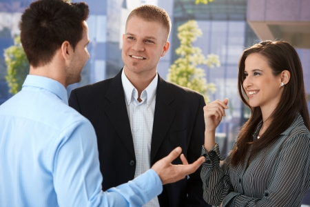chat group: Young businesspeople talking in break time outside of office building, smiling, gesturing. Stock Photo