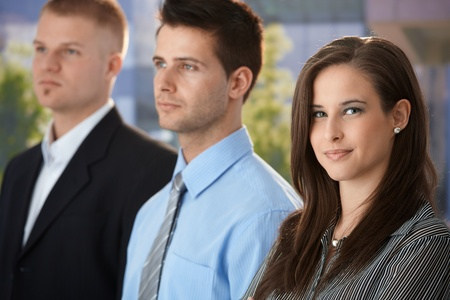 Portrait of smiling businesswoman standing outside of office with colleagues, looking at camera. Stock Photo - 9563939