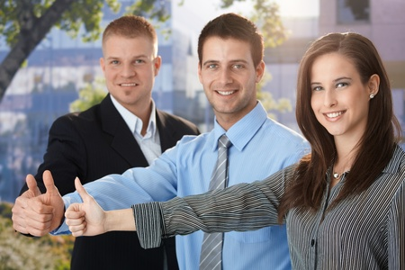 Happy and successful businessteam giving thumb up, outdoor portrait. photo