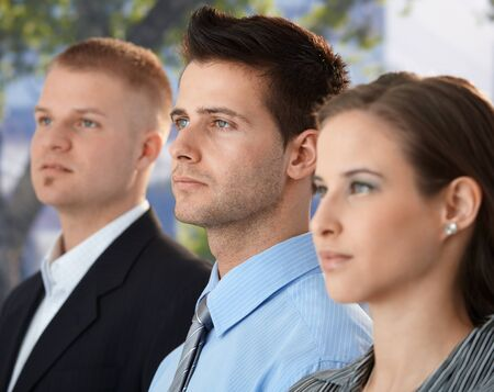 Businessteam outside, concentrating, standing together, focus on young businessman. Stock Photo - 9563025