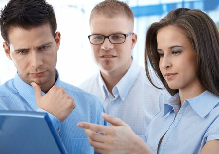 Three businesspeople discussing work in office, looking at laptop computer, thinking, businesswoman pointing at screen. photo