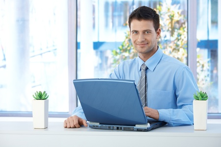 Smiling businessman working on laptop in office, looking at camera confidently. photo