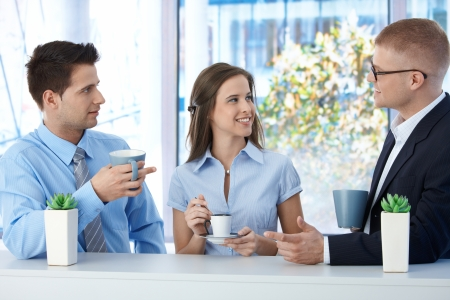 office break: Colleagues on coffee break in business office, talking and smiling. Stock Photo
