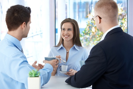 Coffee break in office, coworkers enjoying free time and conversation, smiling. Stock Photo - 9562760