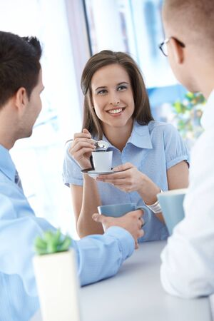 office break: Office workers on coffee break, woman enjoying chatting to colleagues, smiling. Stock Photo