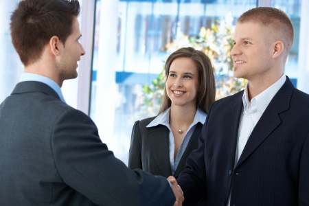 Businesspeople meeting in office, businessmen shaking hand, businesswoman smiling at introduction.