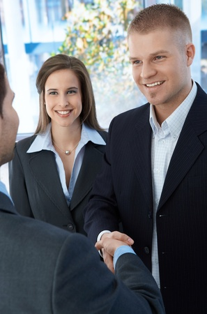 introducing: Business colleagues introducing with handshake, standing in office, smiling. Stock Photo