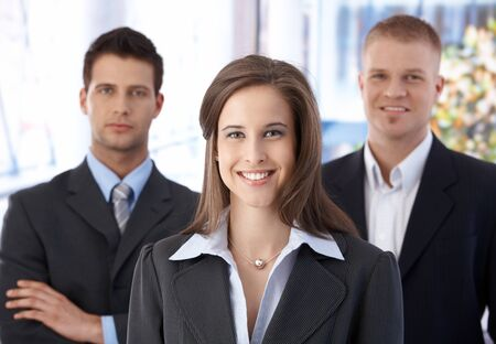 coat and tie: Business team portrait, happy confident businesswoman in focus, businessmen in background. Stock Photo