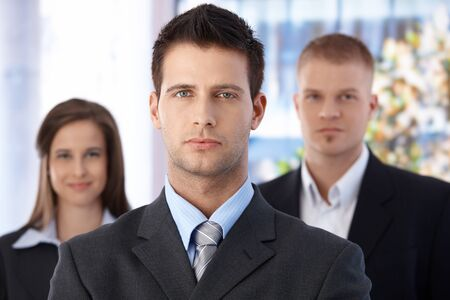 Business team portrait, focus on smart and handsome businessman, coworkers in background. Stock Photo - 9563870
