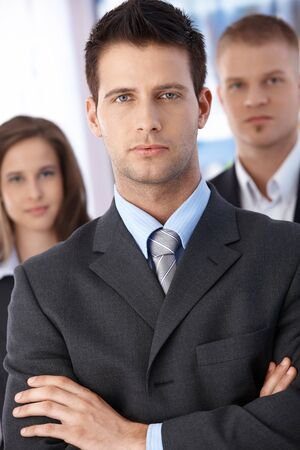 determined: Portrait of determined businessman standing with arms folded, coworkers in background,