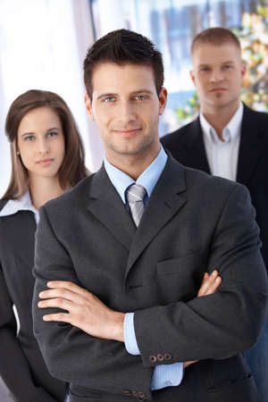 Confident businessteam, focus on smiling elegant businessman standing with arms crossed, looking at camera. photo