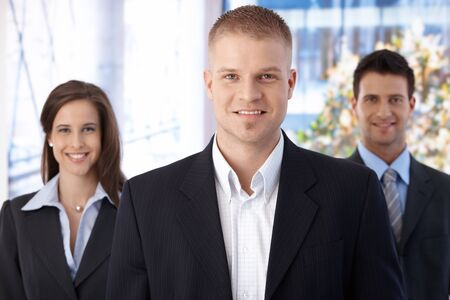 Happy business team standing in office, focus on smiling young businessman looking at camera. Stock Photo - 9562969