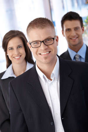 businessteam: Successful trendy young businessteam, standing together, smiling at camera confidently.