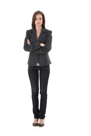 Pretty young businesswoman standing with arms folded, looking at camera, isolated on white, full length. Stock Photo - 9562349