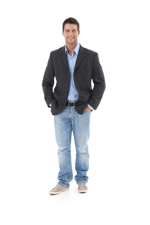 image size: Casual portrait of young businessman, standing with hands in pocket, smiling at camera, isolated on white.