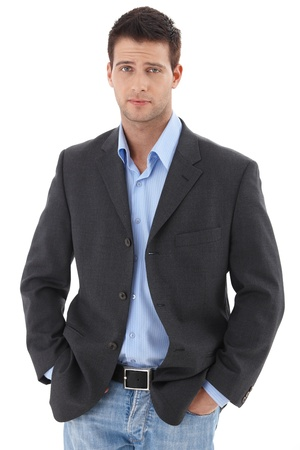 frown: Casual portrait of young charming businessman standing with hands in pocket, looking at camera, frowning.