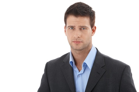 only young adults: Cutout portrait of young handsome businessman, looking at camera, frowning. Stock Photo