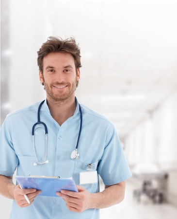 males only: Portrait of handsome young doctor on hospital corridor looking at camera, smiling.�