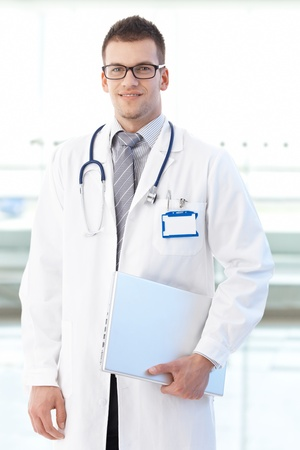 Portrait of smiling young doctor standing on hospital corridor holding laptop, looking at camera.� Stock Photo - 9611522