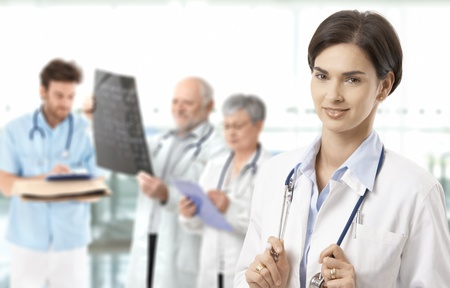 Portrait of middle aged female doctor looking at camera, medical team working in background.� Stock Photo - 9611523