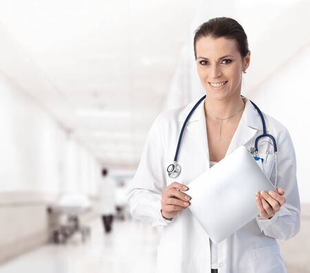 woman doctor: Portrait of woman doctor at hospital corridor, holding tablet computer, looking at camera, smiling.�