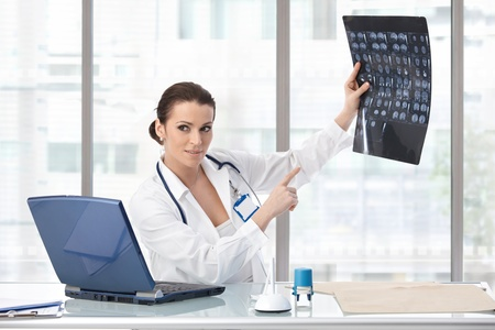 Female doctor sitting at desk explaining medical scan, looking away, smiling.� photo