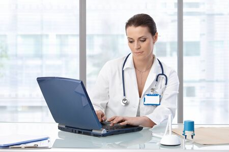 image consultant: Female doctor sitting at table with laptop, looking down, working.�