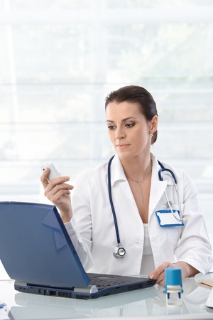 Female doctor sitting at table with laptop, looking at mobile phone, working.� photo