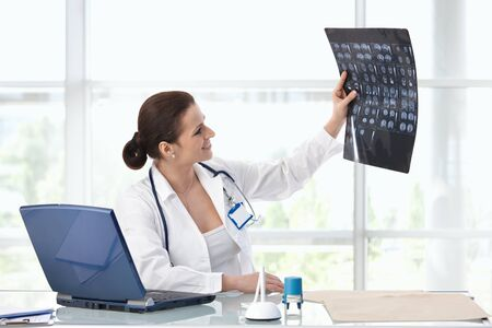 Female doctor working at desk looking at MRI scan.� photo
