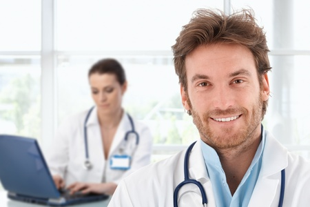 medical cure: Portrait of happy young doctor at clinic, looking at camera, smiling.�