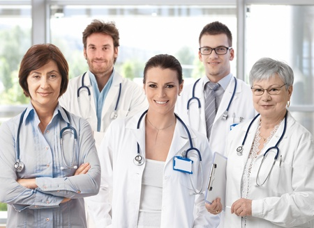 Group of happy doctors in hospital corridor, portrait.� Stock Photo - 9611563