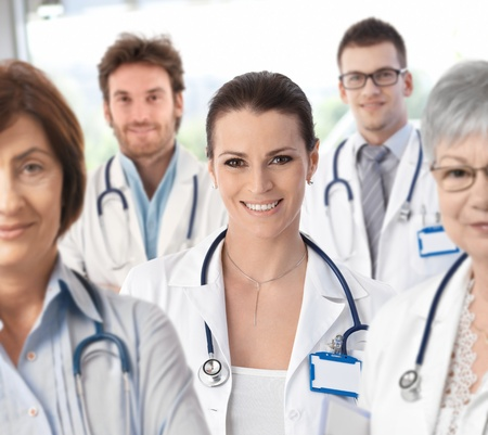 Portrait of female doctor surrounded by medical team, looking at camera, smiling.� Stock Photo - 9611521