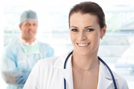 Female doctor and male surgeon, portrait, smiling.� Stock Photo - 9611519