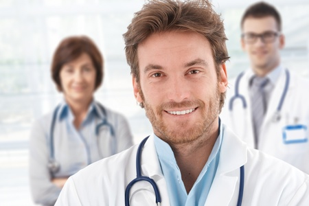 Portrait of happy male doctor with colleagues behind.� photo