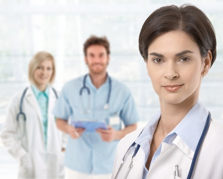 Doctors standing in lobby, female doctor in front.� Stock Photo - 9611560