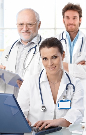 doctor laptop: Doctors working at desk, female doctor in front, looking at camera, smiling.� Stock Photo