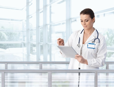 Female doctor using tablet computer in hospital lobby, smiling.� Stock Photo