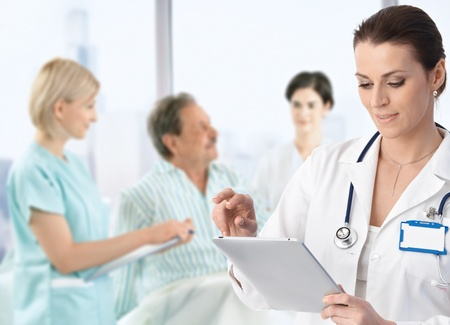 patient and doctor: Doctor recording information to electronic tablet at patients bed, team working in background.�
