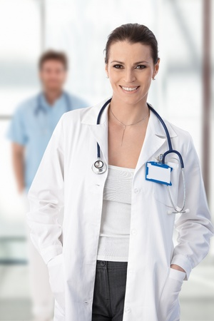 doctora: Doctora permanente con las manos en el bolsillo, sonriente, portrait.?