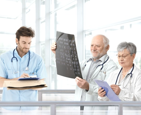 color consultation: Doctors discussing diagnosis in hospital lobby, team lead by experienced professor. Stock Photo